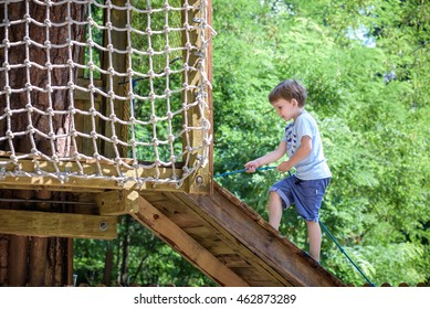 Little toddler boy kid having fun at a wooden playground outdoors.