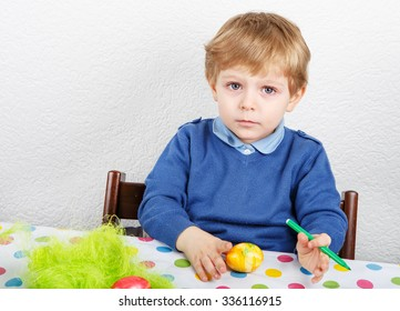 Little toddler boy painting colorful eggs for Easter hunt, traditional action in Germany for Eastern holiday, indoors
