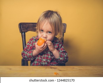 A little toddler boy is peeling a clementine