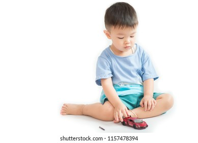 Little toddler boy playing and fixing car toy