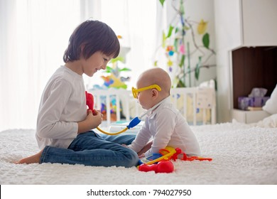 Little toddler boy, playing with his little brother to doctor at home in bedroom
