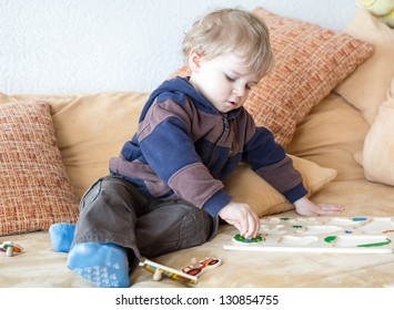 Little toddler boy playing with wooden toys indoor