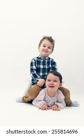 Little toddler boy riding horse on his sister's back