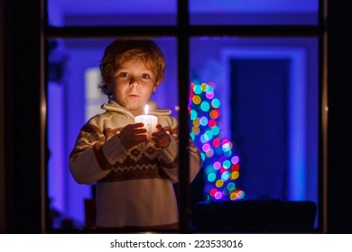 Little toddler boy standing by window at Christmas time and holding candle. With colorful lights from Christmas tree on background, selective focus.