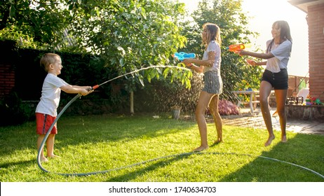 Little toddler boy with two sisters playing with water guns and watering hose on the backyard.