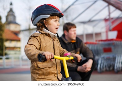 Little toddler child with bicycle and his father in the city. Happy family of two