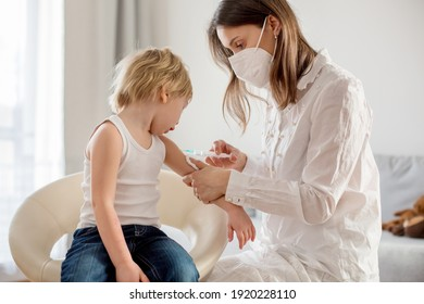 Little toddler child, blond boy, getting injection in consulting room from pediatrition, annual vaccination.