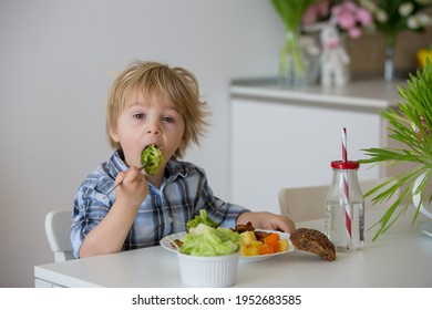 Little toddler child, blond boy, eating boiled vegetables, broccoli, potatoes and carrots with fried chicken meat at home, homemade freshly cooked healthy food