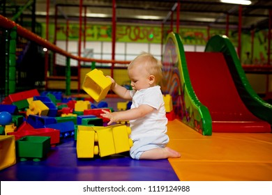 Little toddler child, boy playing in childrens playground indoors, kid plays