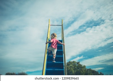 A little toddler is climbing up a slide