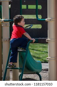 little toddler climbing up stairs on a slide at a playground