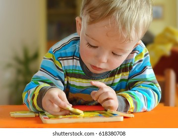 Little toddler doing puzzle. Boy learns to solve problems and develops cognitive skills and . Child concept.