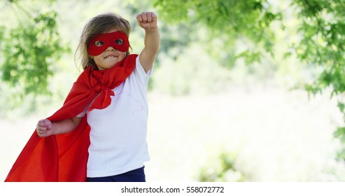 The little toddler dressed as a super hero makes expressions and tries to fly on the green tree background. concept of childhood, game, happiness ,fun, joy  love of nature.