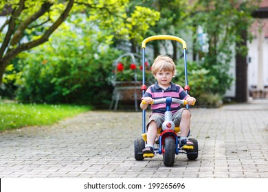 Little toddler driving tricycle or bicycle in home garden