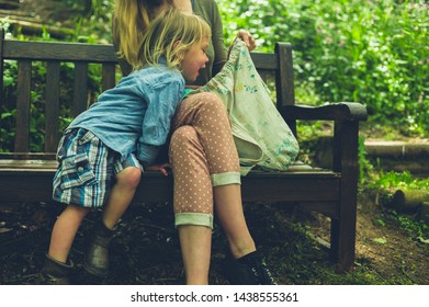 A little toddler is getting something from his mother's bag as thery are sitting on a bench in the woods
