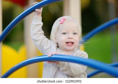 Little toddler girl having fun at a playground