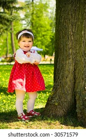 Little toddler girl laughing near the tree