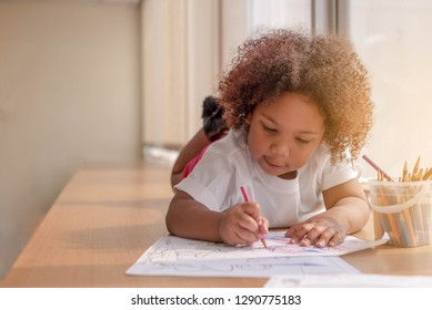 Little toddler girl laying down concentrate on drawing.  Mix African girl learn and play in the pre-school class. Children enjoy hand writing. 3 years girl enjoy playing at nursery.