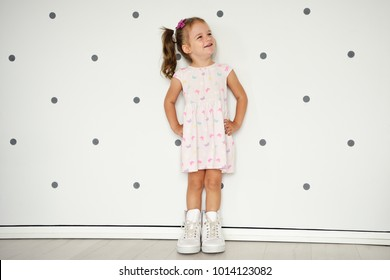 Little toddler girl in light dress and big daddy's shoes is standing near the wall, looking up and having fun. Happy smile of kid. Free space for childhood concept.