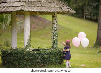 Little toddler girl with pink birthday balloons walking near a wishing well outdoors