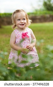 Little toddler girl in pink dress smiling