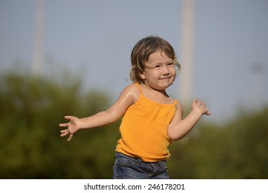 little toddler girl playing and posing in the summer rain