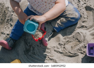 Little toddler girl playing in the sand with boxes and sand shovel