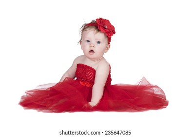 little toddler girl in a red netting dress with a red flower in her hair isolated on a white background in studio