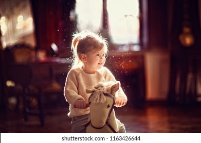 Little toddler girl sitting on toy horse before backlight from window. Happy smiling child playing at home