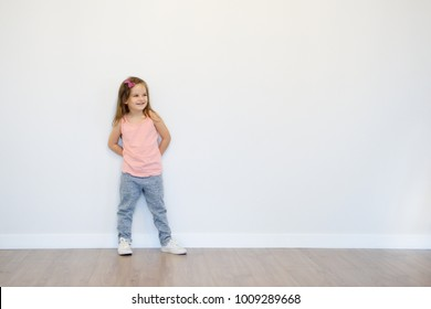 Little toddler girl is standing near the wall, looking to side and having fun. Happy smile of kid at home. Free space for text and childhood concept.
