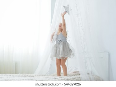 Little toddler girl standing on bed in white bedroom. Cute baby in nice dress touching a star.