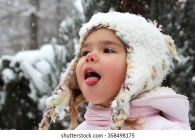 Little toddler girl in warm coat and knitted hat having fun in the winter forest and trying to catch snowflakes with her mouth, outdoor portrait