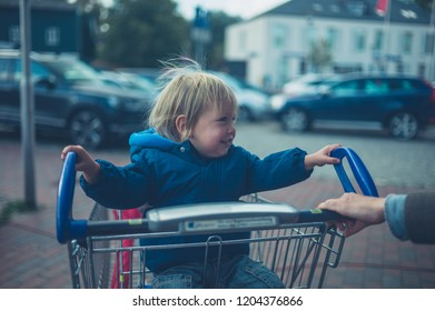 A little toddler is having fun riding in a shopping cart