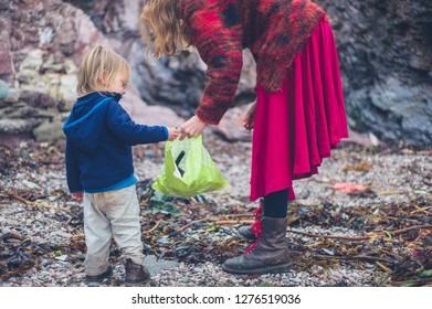 A little toddler is helping his mother clean up plastic rubbish on the beach