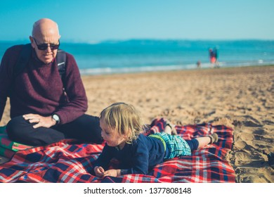 A little toddler and his grandfather are relaxing on the beach