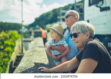 A little toddler and his grandparents are looking over a wall in a town