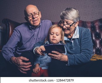 A little toddler and his grandparents are sitting on a sofa looking at a smartphone