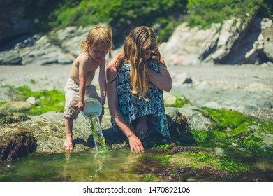 A little toddler is on the beach with his mother and is splashing water from a bucket