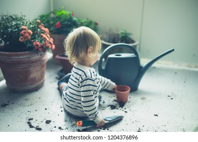 A little toddler is playing with dirt and a watering can