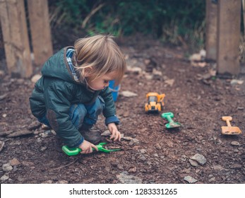 A little toddler is playing outside in winter