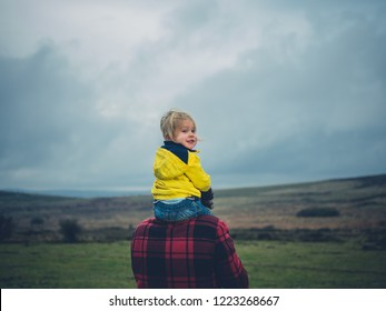 A little toddler is riding on his father's shoulders on the moor