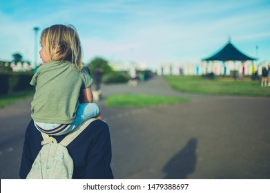 A little toddler is riding on his mother's shoulders at sunset in the park