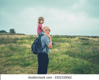 A little toddler is riding on the shoulders of his grandfather outdoors in nature on a summer day