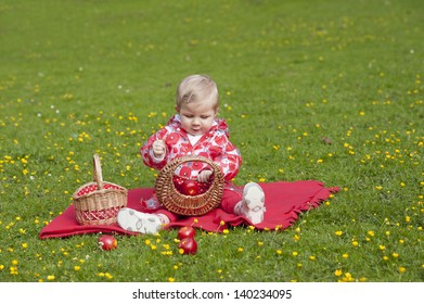 little toddler seated outdoors, in grass with buttercups