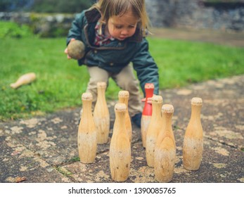 A little toddler is setting up some bowling pins outdoors