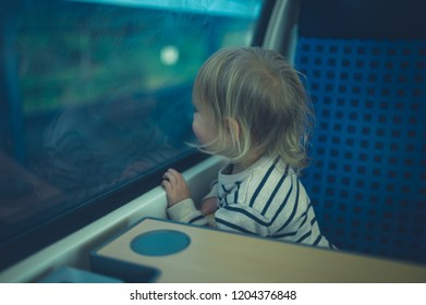 A little toddler is sitting by the window on a train