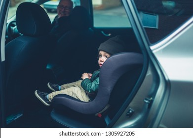 A little toddler is sitting in his car seat waiting to drive off