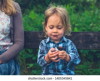 A little toddler is sitting on a bench in nature with his mother and is eating a fruit bar