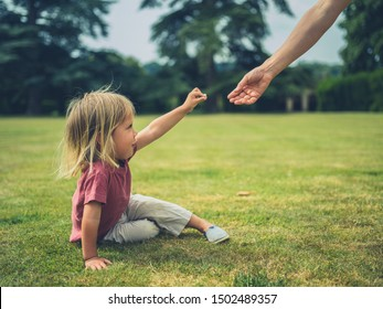 A little toddler is sitting on the grass in a park and is offering his mother a flower