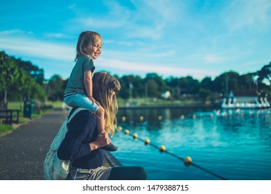 A little toddler is sitting on his mother's shoulders by a lake in a park at sunset